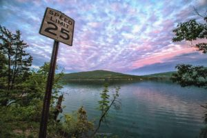 speed limit sign and sunset over lake