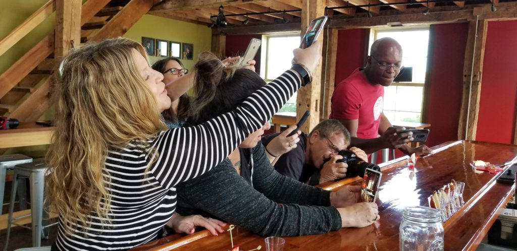 several bloggers taking a photo of drinks at a bar