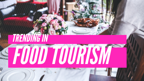 Trending in Food Tourism in white text with pink lines behind it set against a dinner table.