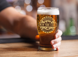 a glass of beer with the NYSBA logo