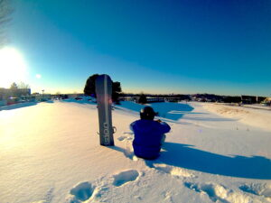 Snowboarder sitting at the top of a run